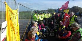 Group sat with line of police beside